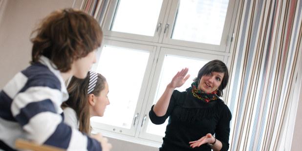 Lærer diskuterer med to elever.