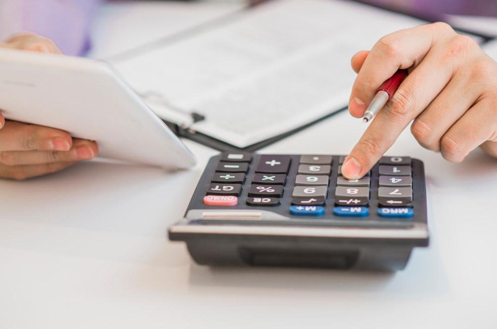 En hånd taster på en kalkulator. Den andre hånden holder et ark. Vedkommende sitter ved et bord med en bok på.