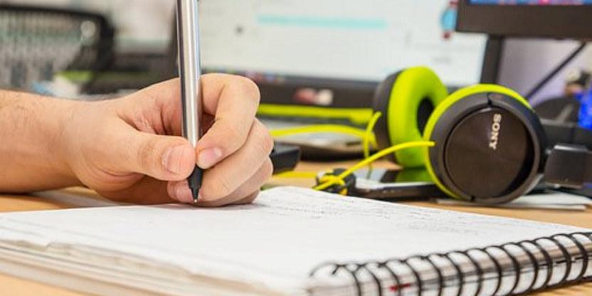 Bilde av en hånd som ligger på en notatblokk. Hånda holder en penn. Vi ser en pc og hodetelefoner i bakgrunnen