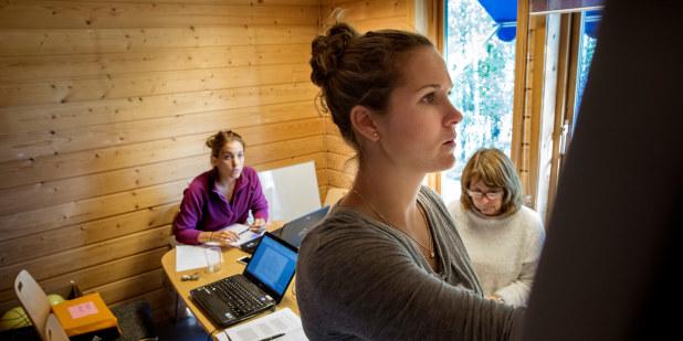 Tre kvinner samarbeider i møterom