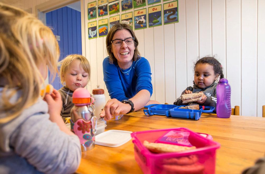Tre barn sitter rundt et bord i en barnehage sammen med en kvinnelig barnehagelærer som smiler.  De spiser matpakkene sine.