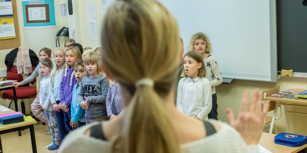 Bilde av kvinnelig lærer foran mange elever.