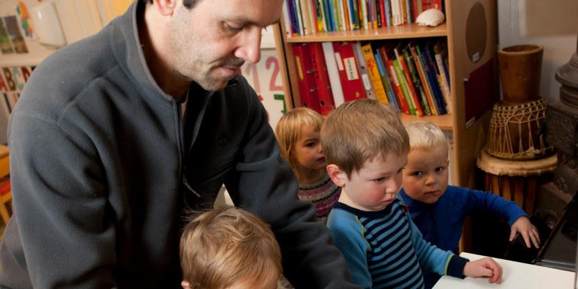 En middelaldrende mann veileder 4 små barn i en barnehage.