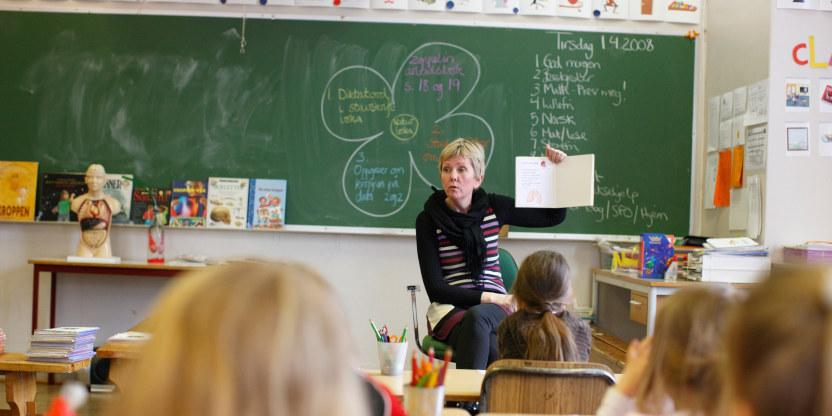 En kvinnelig lærer i klasserommet holder opp et ark foran en klasse med yngre barn.