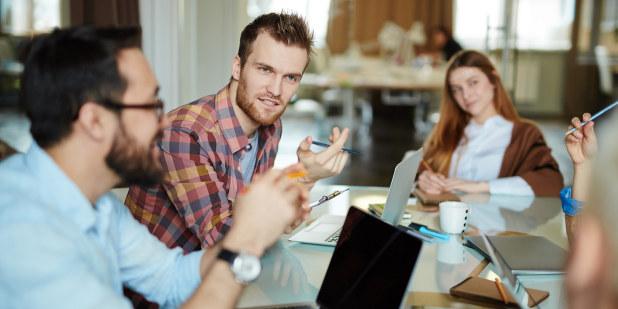 Bilde av tre unge lærere sittende i samtale.
