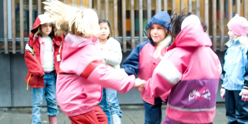 Bilde av barn som holder hverandre i hendene i en sirkel og leker utenfor en skole.