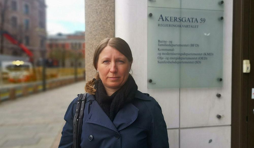 En alvorlig Guro Elisabeth Lind  ser i kamera med et skilt med Akersgata 59 bak seg.