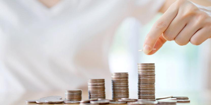 En person sitter ved et bord og legger penger på fire myntstabler.