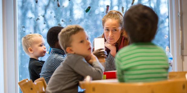 Bilde av barnehagelærer som sitter ved et bord sammen med flere barn.