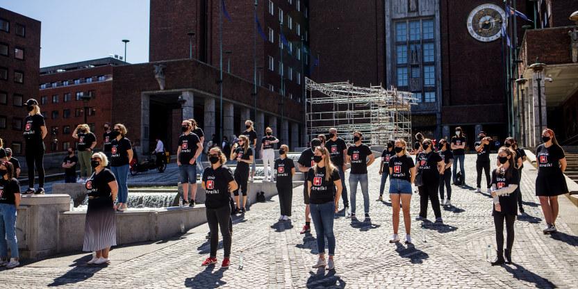 Streikende utenfor borggården i Oslo rådhus iført streike t-skjorte står med avstand mellom seg og med munnbind, under en streikemarkering.