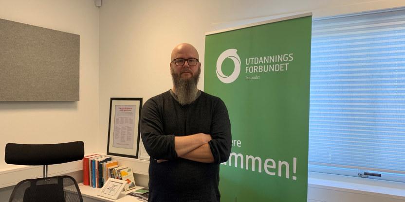Bilde av Thore Johan Nørbøe med armene i kryss på kontoret foran en rollup med logo fra Utdanningsforbundet Innlandet