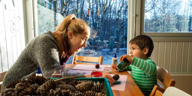 Bilde av barnehagelærer i engasjert samspill med barn sittende ved et bord.