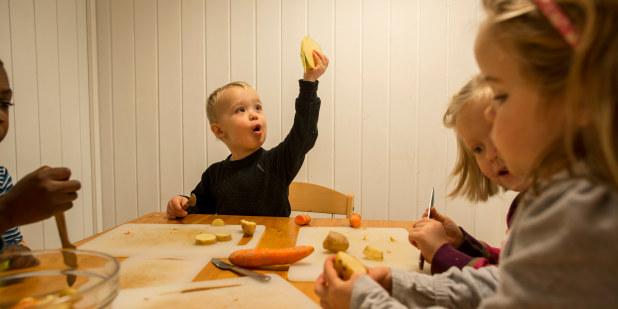 Barnehagebarn som sitter ved et bord og kutter opp grønnsaker.
