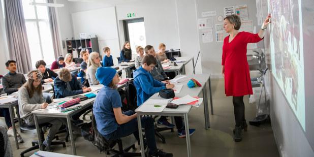 Lærer står foran en klasse, mens hun peker på tavlen.
