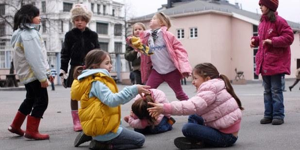 Bilde av noen barn som sitter på bakken på skolegården. De leker med hverandre