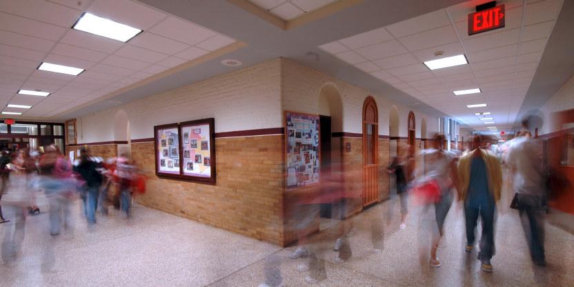 To korridorer i skolebygg som møtes. Elever i bevegelse begge veier, noen av dem er uklare i bildet.
