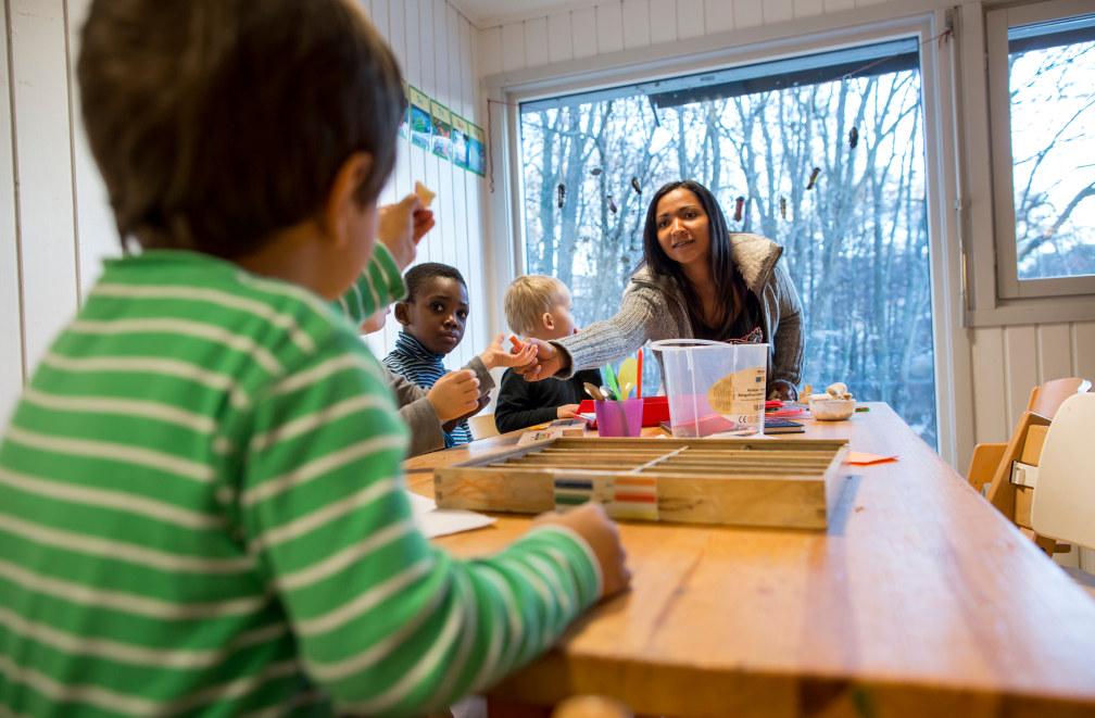 Barn sitter rundt et bord i en barnehage. En barnehaglærer sitter ved bord-enden og gir noe til et av barna.