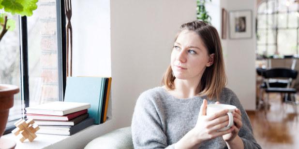 Jente i stol med kaffekopp