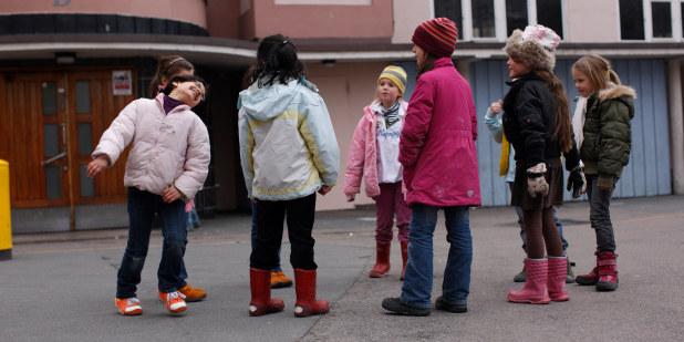 Barneskoleelever som står i en ring i skolegården.