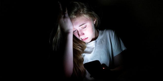 fortvilet ung jente med mobiltelefon i mørket