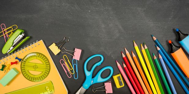 Bilde med fargestifter, saks og annet skoleutstyr liggende på en pult