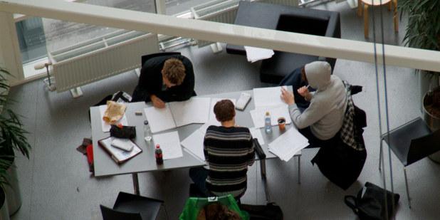 Tre studenter som gjør skolearbeid ved et møtebord.