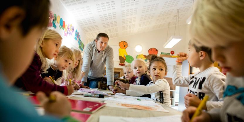 Mange barnehagebarn sitter rundt et bord. En mannlig barnehagelærer står ved enden av bordet og snekker med dem.