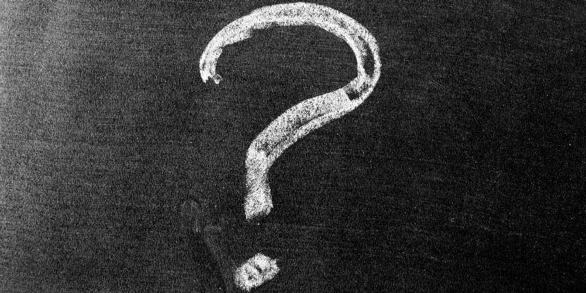 Bilde av spørsmålstegn tegnet med hvitt kritt på svart tavle.