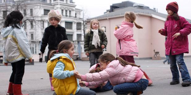Bilde av syv barn som leker i en skolegård. To sitter foran på bakken, de andre leker i bakgrunnen.
