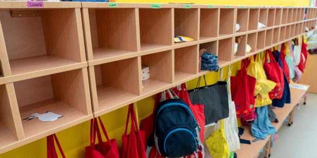 Bilde av en garderomb hvor vi ser hyller etter hverandre, med knagger under som det henger barneklær på. En typisk garderobe fra en barnehage