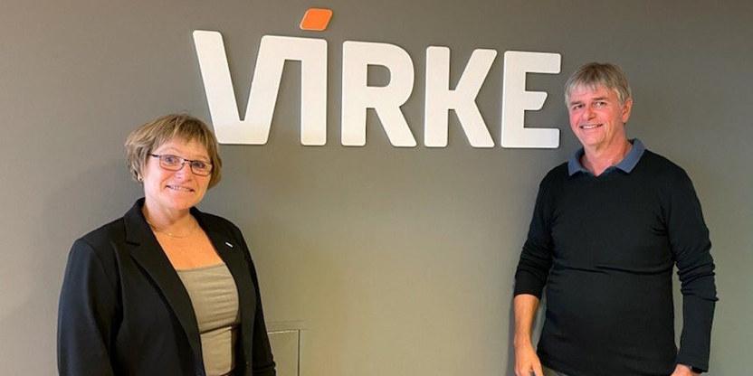 Bilde av forhandlingsleder for Virke, Anne Torunn Tallaksen, og forhandlingsleder for Unio Virke, Bjørn Sævareid, foran en vegg der logoen til Virke står.
