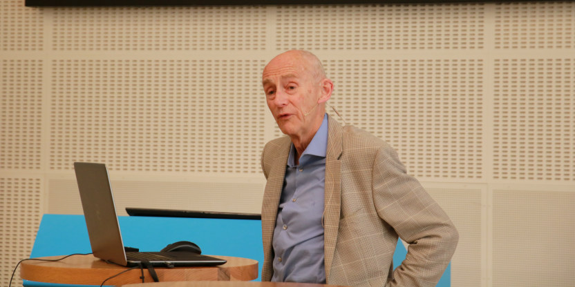Nærbilde av professor emeritus Jan Fridthjof Bernt. Han har på lyseblå skjorte og grå jakke. Står og holder foredrag i Lærernes hus.