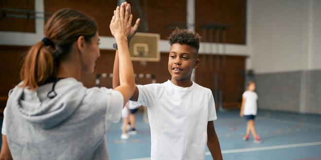 """Illustrasjonsfoto av kvinnelig kroppsøvingslærer som gir en """"high five"""" til en elev"""
