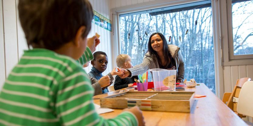Barn sitter rundt et bord i en barnehage. Den nærmeste gutten med ryggen til kameraet strekker ut hånda for å ta i mot noe som gis ham av en voksen kvinne ved bordenden.