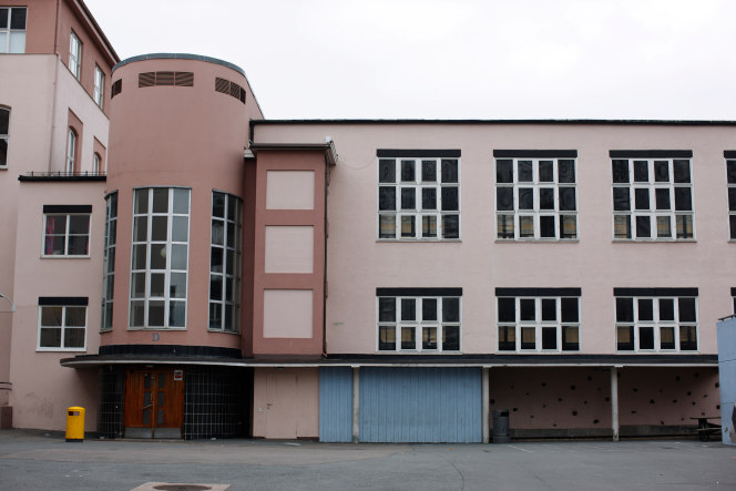 Bilde av et nøytralt skolebygg, hvor du kan se en fargeløs vegg med vinduer, samt en asfaltert skolegård i forkant.