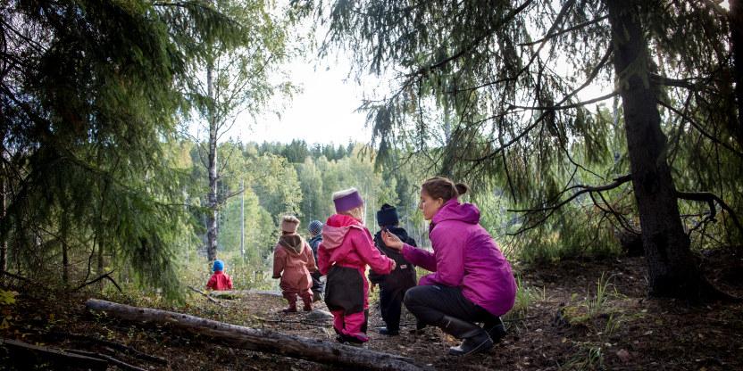 Barnehagebarn på tur i en skog. I forgrunnen sitter en voksen kvinne på kne og prater med et av barna. Alle har på seg regntøy.