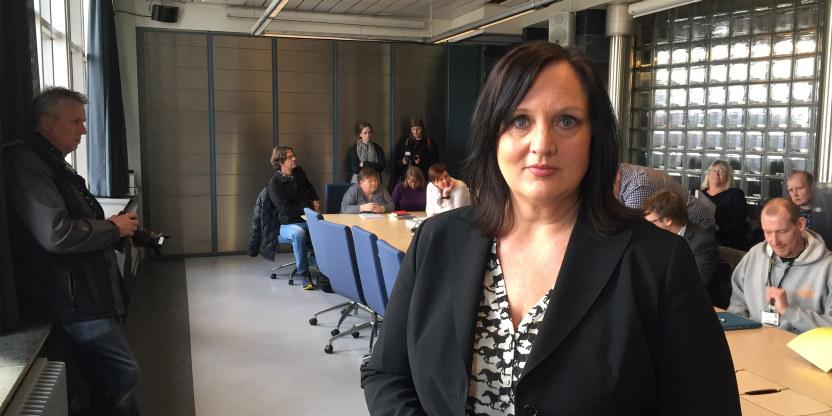Forhandlingsleder Aina Skjefstad Andersen ser mot kamerat med mange mennesker bak seg rundt et bort i Oslo Rådhus.
